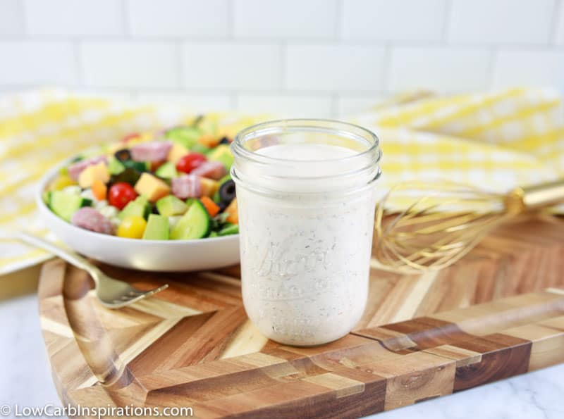 close up of keto ranch dressing recipe in a mason jar with a salad in the background