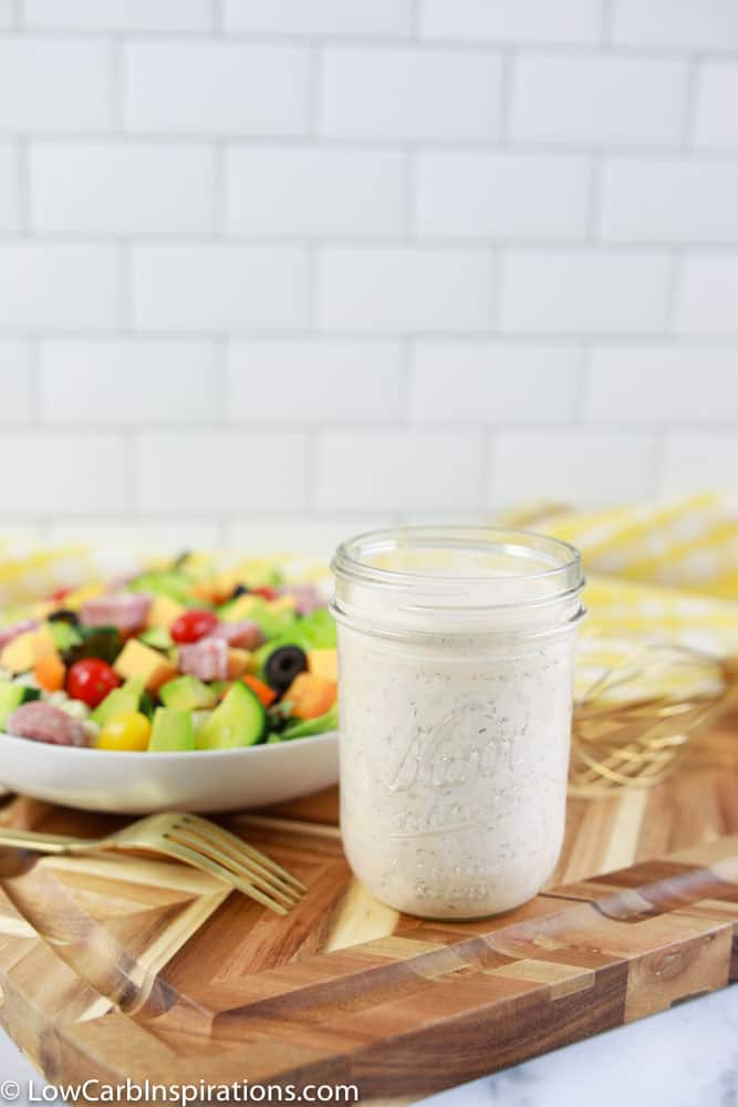 keto ranch dressing recipe in a mason jar with a salad in the background