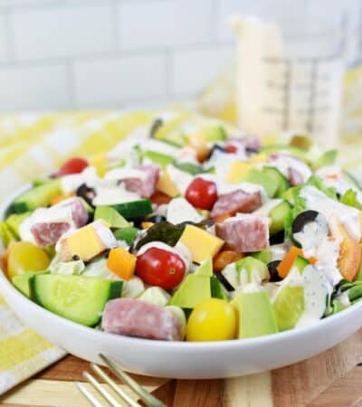 close up of keto salad dressing recipe on a salad with ranch dressing in the background