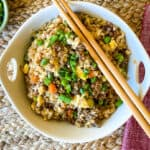 Bowl of fried rice with chopsticks and a red napkin