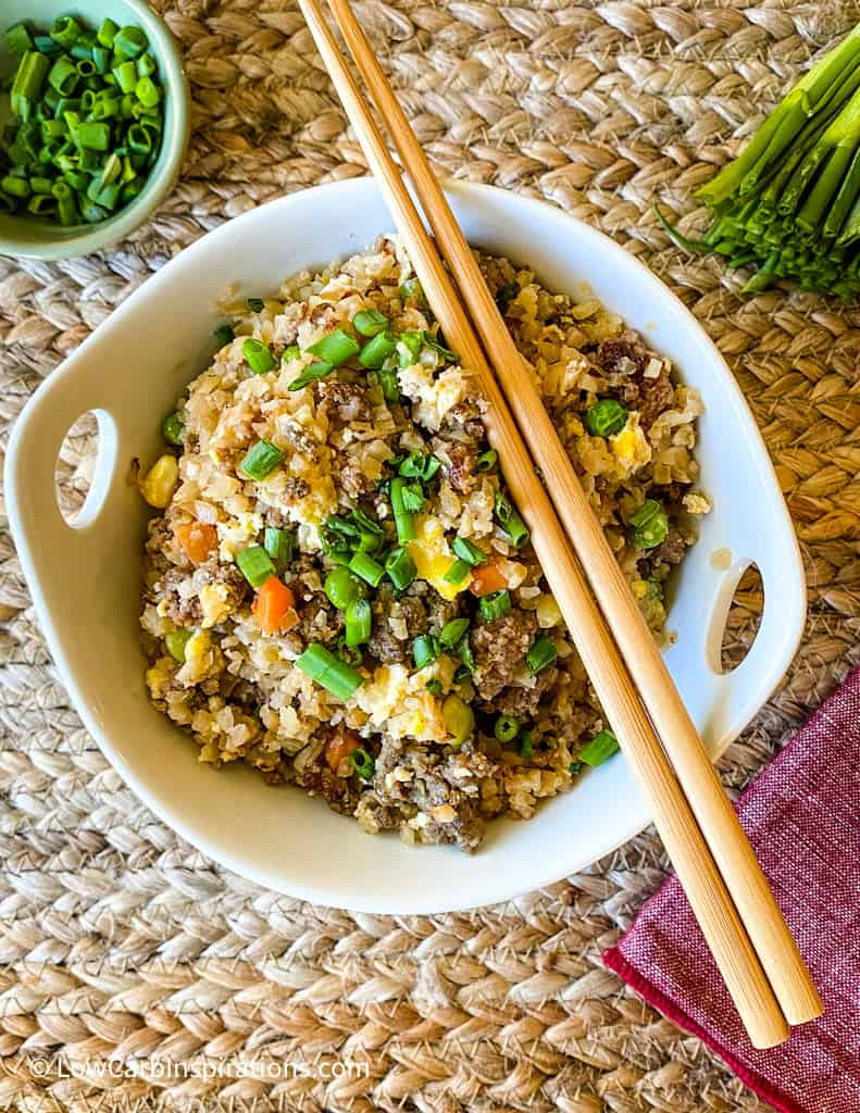 Bowl of fried rice with chopsticks and a side bowl of chive onions