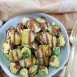 overhead photo of crispy brussel sprouts on a blue plate drizzled with mustard vinaigrette
