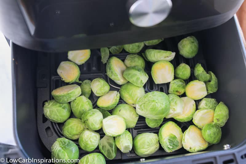 cut and trimmed brussels sprouts in an air fryer ready to be cooked