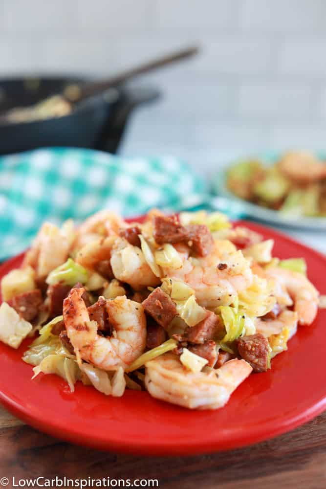 close up of cajun shrimp, sausage and cabbage skillet dinner on a red plate
