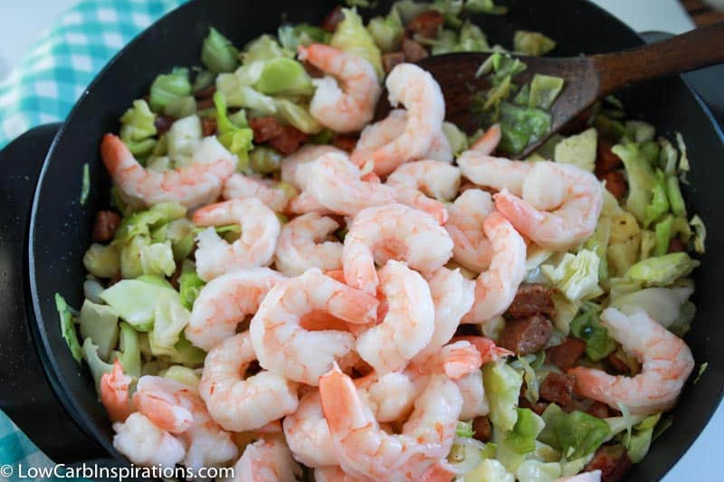 adding shrimp and cooking cooking sausage and cabbage cooking in a skillet with a wooden spoon