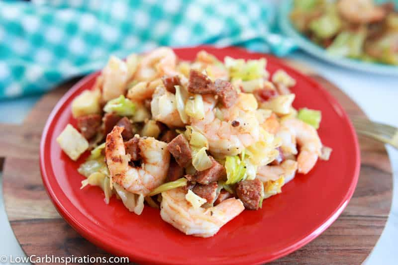 cajun shrimp, sausage and cabbage skillet dinner on a red plate