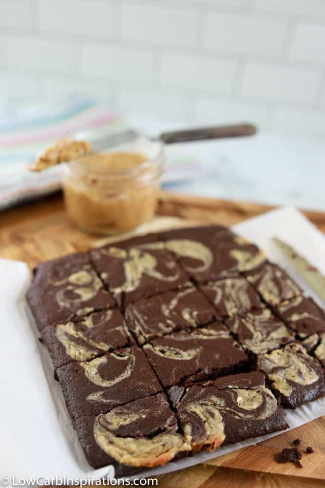 peanut butter swirl brownies on a wood cutting board cut into squares with more peanut butter in the background