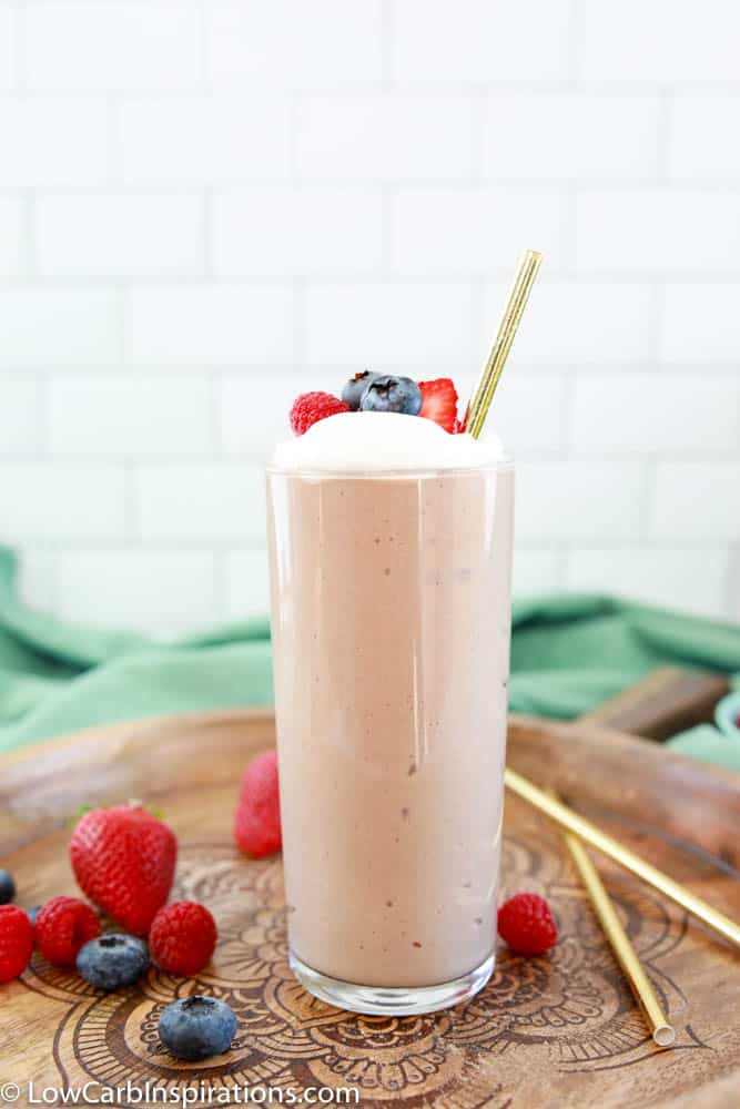 side photo shot of the easy protein shake recipe in a clear class on a wood board with berries on the side
