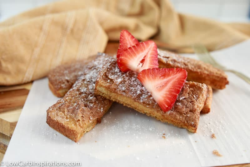 air fryer french toast sticks on parchment paper with strawberries on top