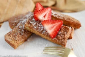 close up of air fryer french toast sticks on parchment paper with strawberries on top