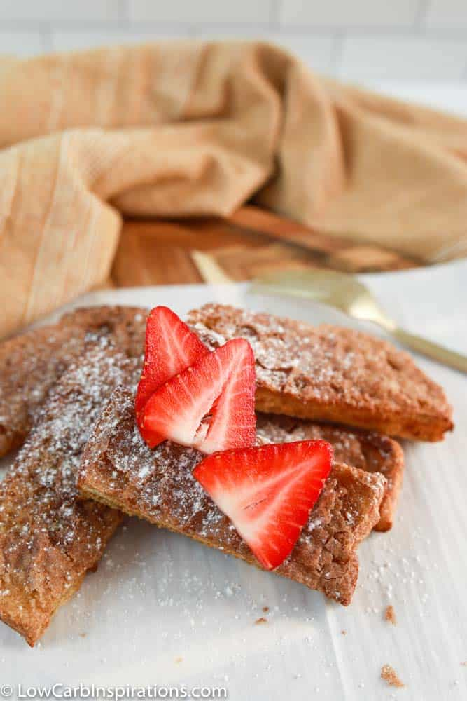 finished air fryer french toast sticks on parchment paper with strawberries on top