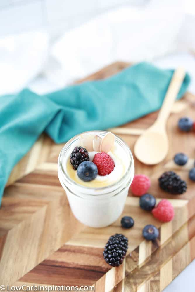 coconut yogurt recipe ready to eat with a wood spoon and mixed berries on the side