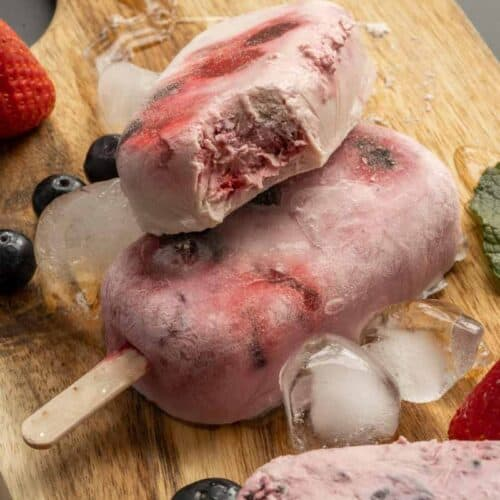 close up of Keto Triple Berry Popsicles on a wooden board