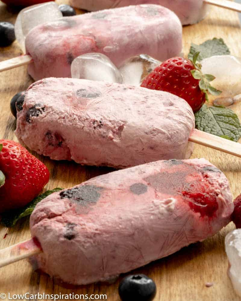 close up of whole fruit popsicles on a wooden board with berries and ice on the side