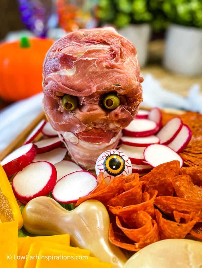 Skeleton head on a charcuterie board wrap in meat